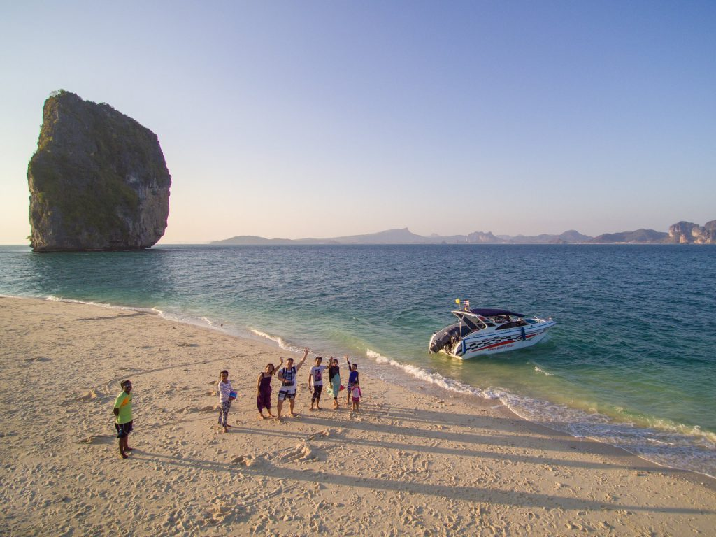 aerial photo of group of people waving by a speedboat on a beach at sunset in krabi